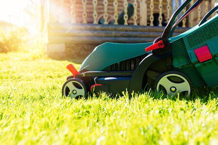 Foto de Green electric lawn mower on a freshly mown lawn in the garden against the background of a village house with flare light - Imagen libre de derechos