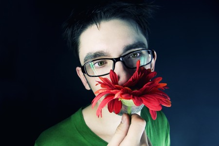 young guy with a red flower on a black background