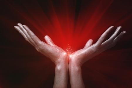 Photo pour Silver men's hands holding red magic glow on black background - image libre de droit
