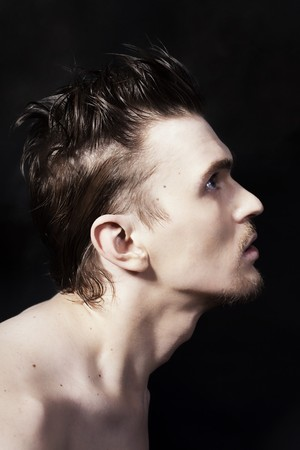 Profile of a young handsome man on black background