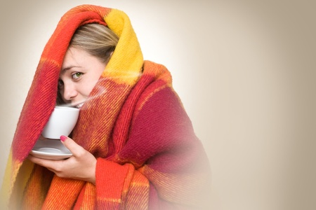 Photo for A young woman caught a cold, wrapped in a blanket and something hot drink from a cup. - Royalty Free Image