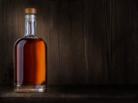 Photo pour Bottle of whiskey on a wooden background with copy space - image libre de droit