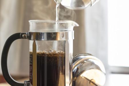 Foto de Coffee brewing in a French press in warm morning light; - Imagen libre de derechos
