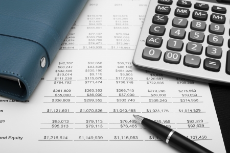 business financial chart analysis with pen, notebook & calculator on paper work