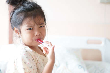Asian child or kid girl Influenza A sick and eating or taking red drug or water medicine by syringe pump and make face bitter on bed at hospital room for pediatric patient treatment and healthcare