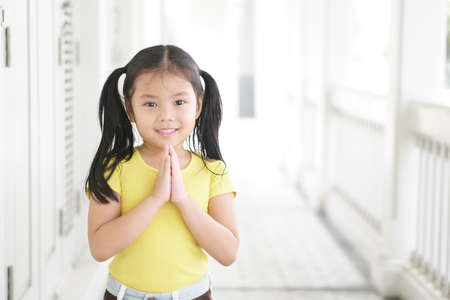 Photo for Asian child smiling hand in hand or kid girl pay obeisance and pray or hello welcome and thank you with wear yellow shirt in morning at church or temple for peace on white and receptionist at hotel - Royalty Free Image