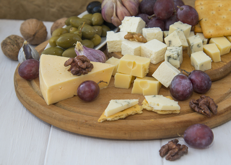 Cheese plate with a variety of cheese, grapes, olives and nuts