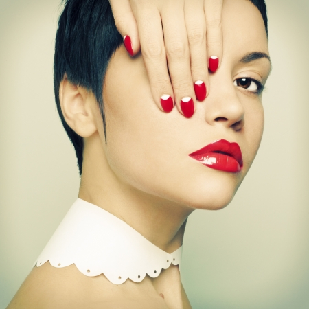 Fashion portrait of a beautiful young lady with bright nail polishの写真素材