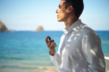 Handsome young man spray perfume. Fashion photo