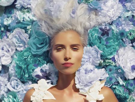 Foto de Beautiful blonde young woman lying in flowers - Imagen libre de derechos