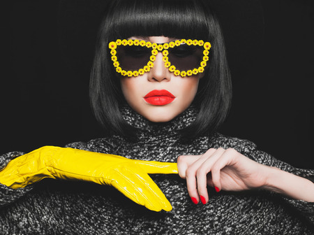 Fashion studio photo of stylish lady in gloves and sunglasses