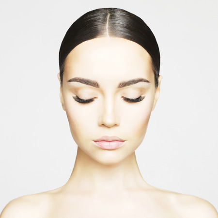 Studio portrait of beautiful young woman with perfect skin. Beauty and care. Extension eyelashes. Spa salon