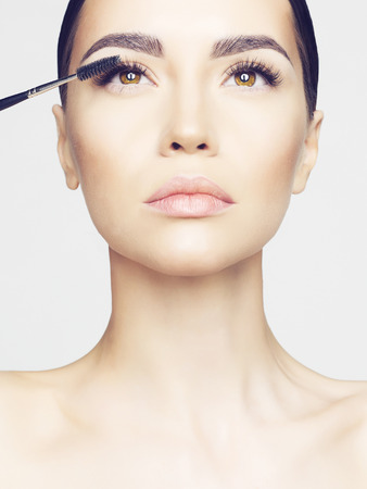 Photo pour Studio fashion photo of beautiful young lady applied mascara.  Beauty and care. Extension eyelashes. Spa salon. Perfect face makeup - image libre de droit