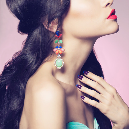 Photo pour Fashion studio portrait of beautiful young woman with earring. Beauty and manicure. Jewelry and accessories - image libre de droit