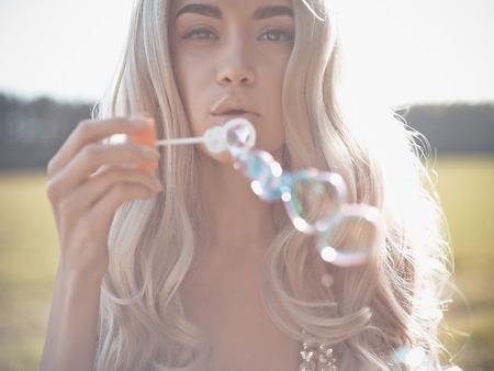 Photo pour Outdoors fashion photo of beautiful blonde blowing bubbles - image libre de droit