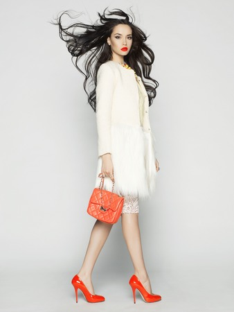 Beautiful brunette model in fashion clothes posing in studio. Wearing coat, handbag, red shoesの写真素材