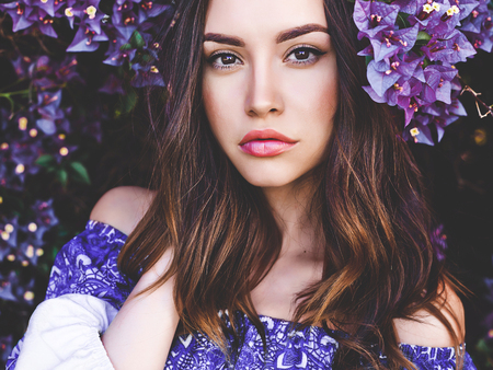 Outdoor fashion photo of beautiful young woman surrounded by flowersの写真素材