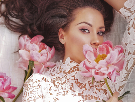 Foto de Stylish fashion photo of beautiful young woman lies among peonies. Holidays and Events. Valentine's Day. Spring blossom. Summer season - Imagen libre de derechos