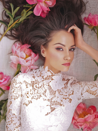 Stylish fashion photo of beautiful young woman lies among peonies. Holidays and Events. Valentine's Day. Spring blossom. Summer season