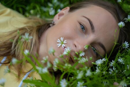Beautiful young woman lying on the grass against the background of flowers in the forest