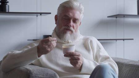 Photo pour A handsome elderly man with a gray beard eats yogurt holding a spoon close to his mouth - image libre de droit