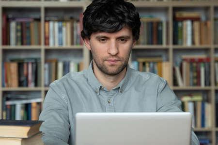Foto de Male student using laptop studying in the university library - Imagen libre de derechos