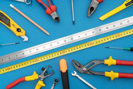 Various tools for repair, a tool kit for the home, on a blue background, safe work for construction.