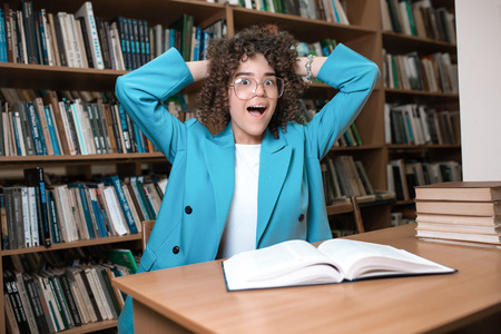 Photo pour Young beautiful curly girl in glasses and blue suit sitting with books in the library. Student Study - image libre de droit