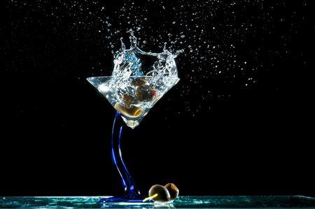 Photo pour Splash of olives into a glass of martini. - image libre de droit