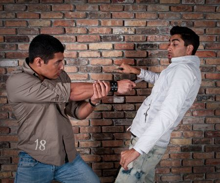 Young guys fighting in the street with knifes.