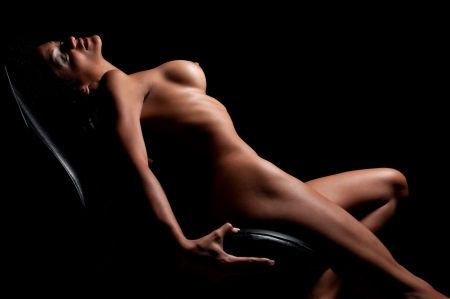Young brunette posing nude in dim light.