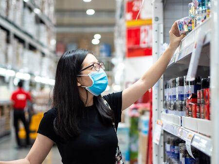 Photo pour New normal, young asian women wearing mask shopping in the store during coronavirus pandemic crisis. - image libre de droit