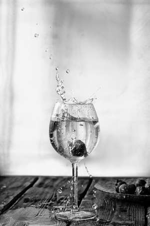 Victoria berry falls into a wine glass and splashes fly from the glass