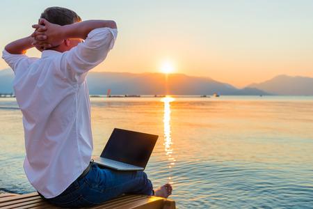 Foto de Recreational entrepreneur. Man with laptop in the morning on the beach working - Imagen libre de derechos