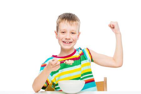 Photo pour concept - proper nutrition, a strong healthy boy shows biceps, eats porridge - image libre de droit