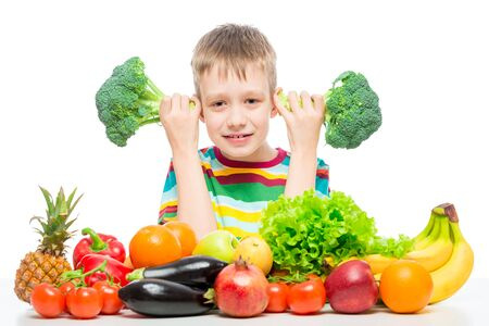 Photo for Boy 10 years old with broccoli and a bunch of vegetables and fruits posing in the studio isolated on white background - Royalty Free Image