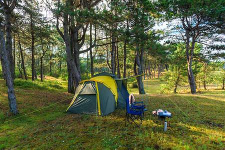Foto de camping tent in a pine forest by the sea - Imagen libre de derechos