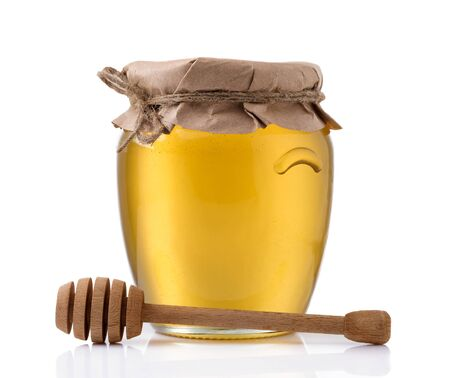 Glass jar full of honey and wooden stick on a white background.の写真素材