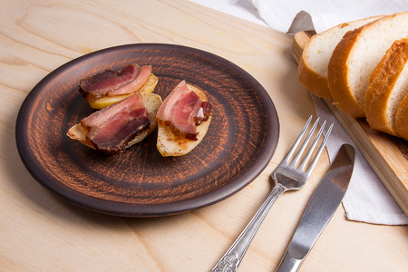 Tasty baked potatoes with slices of bacon in brown clay plate on wooden background. Slices of smoked bacon on potatoes. Slices of white bread on cutting board. Eating utensils fork and knife near with plate.