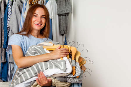 Photo pour Happy caucasian woman holding bunch of wooden hangers with sorted cotton and wool shirts. - image libre de droit