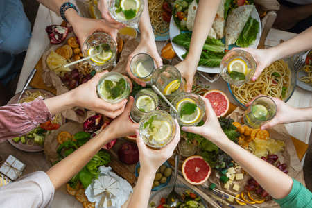 Photo pour Top view closeup female friends hands cheers toasting glass of healthy beverage over serving table - image libre de droit