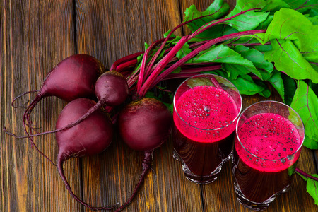 Glass of fresh beetroot juice with bets on wooden table.