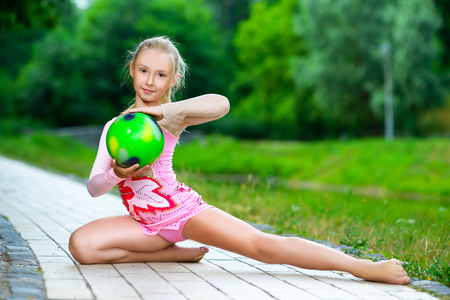 outdoor portrait of young cute little girl gymnast training with ball in park.
