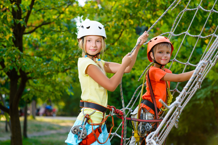 Photo pour Cute children. Boy and girl climbing in a rope playground structure at adventure park. - image libre de droit