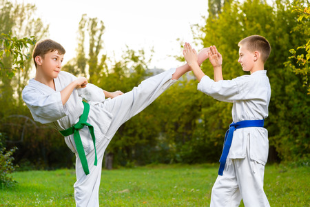 boys in white kimono during training karate exercises at summer outdoors.