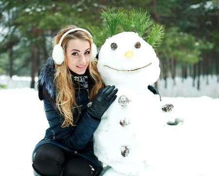 Pretty girl with snowman in pinewood on a winter day