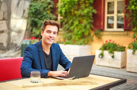 Photo pour Charming young business man outdoors at a table in a summer cafe courtyard working at a laptop - image libre de droit