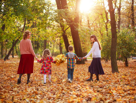 Photo for Happy family, mother with children, daughters and son are walking through the fallen leaves of the autumn city forest park - Royalty Free Image