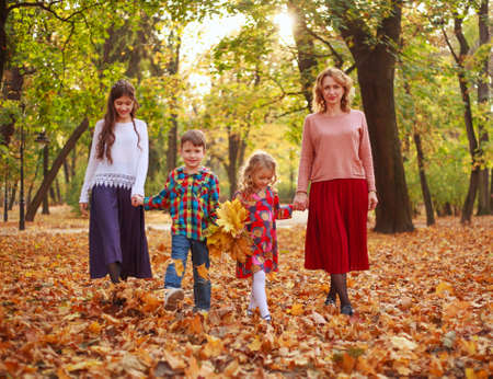 Photo pour Happy family, mother with children, daughters and son are walking through the fallen leaves of the autumn city forest park - image libre de droit