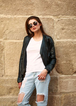 Foto de Young girl in trendy retro 90s style leather jacket and jeans on the street of the old city - Imagen libre de derechos